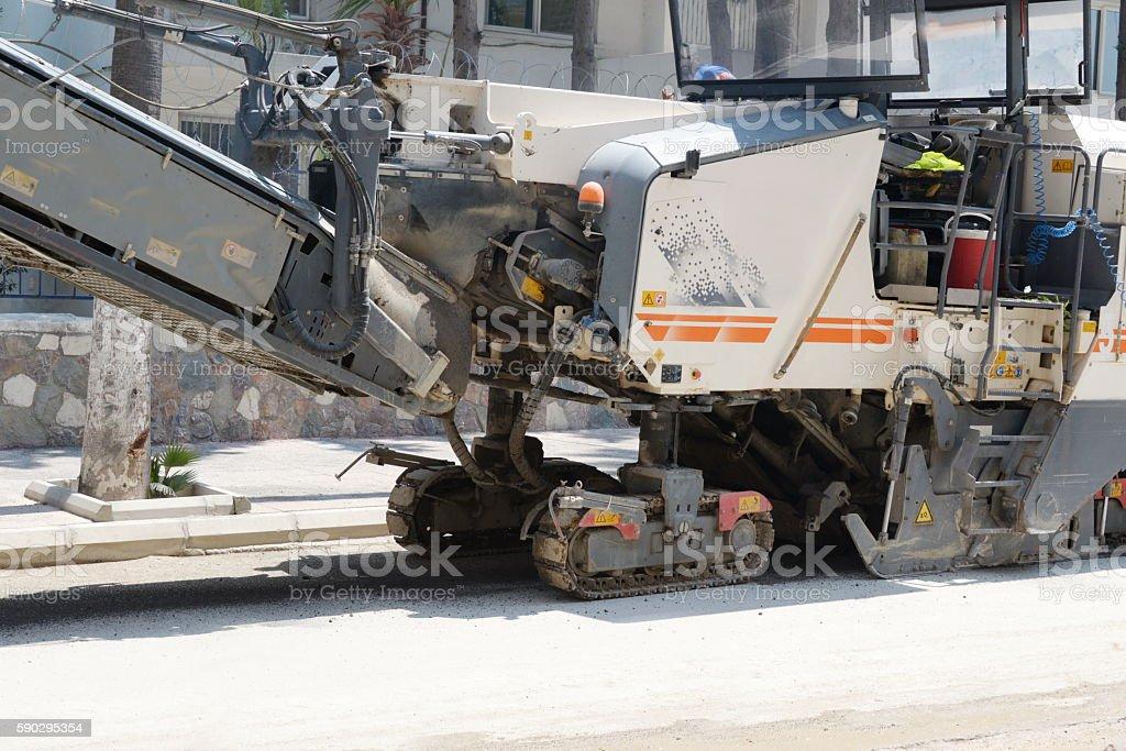 Asphalt removing machine loading powdered asphalt on the truck royaltyfri bildbanksbilder