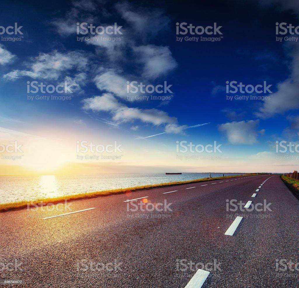 Asphalt road along the sea at sunset. – Foto