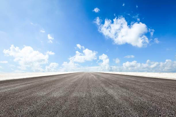 asphalt road and blue sky and white clouds scene - prospettiva lineare foto e immagini stock