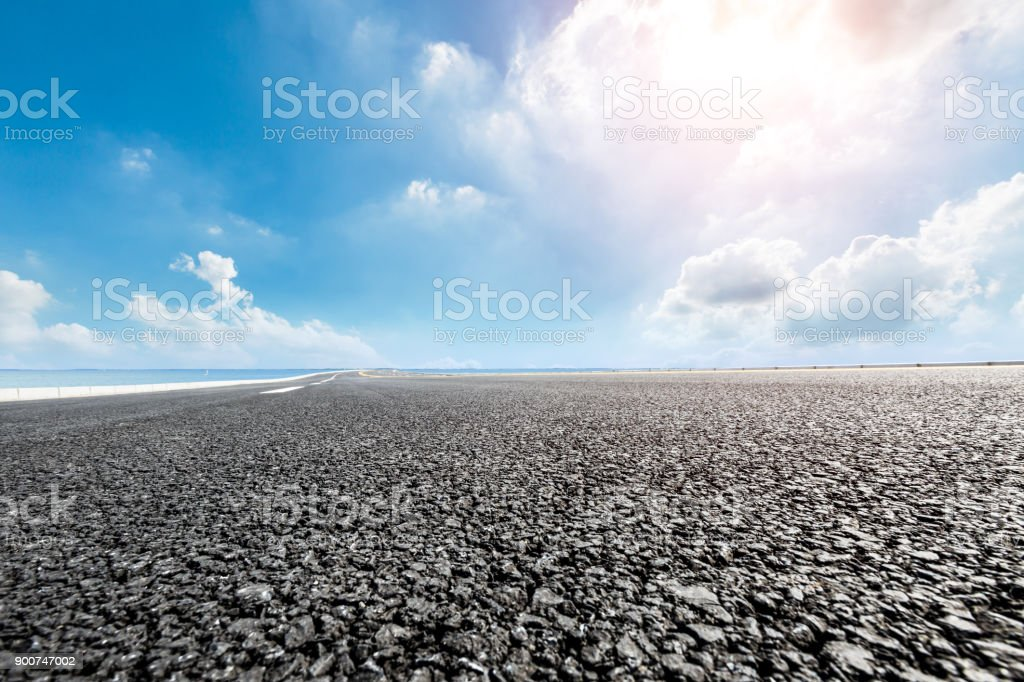 new asphalt road and blue sky with white clouds by the lake