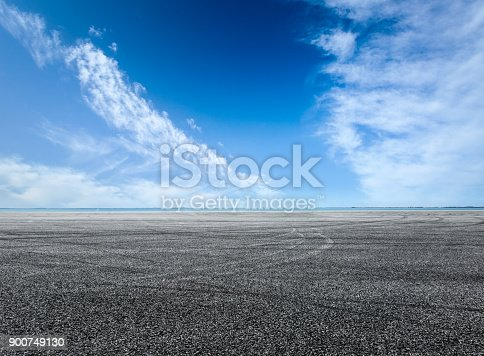 621693226istockphoto asphalt road and blue sky with white clouds by the lake 900749130