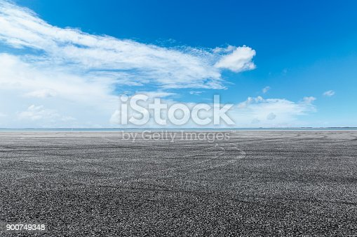 621693226istockphoto asphalt road and blue sky with white clouds by the lake 900749348