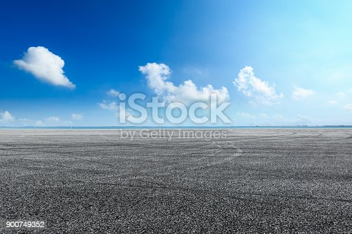 621693226istockphoto asphalt road and blue sky with white clouds by the lake 900749352