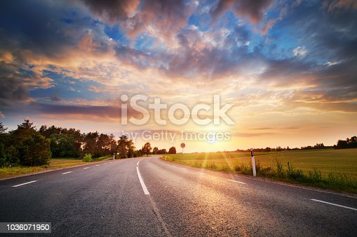 black asphalt road and white dividing lines at sunset
