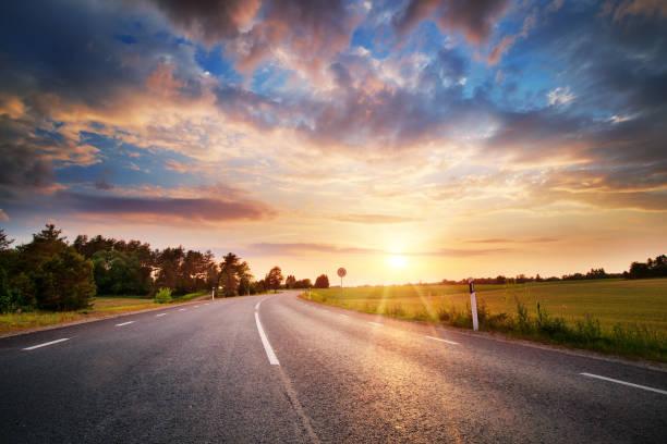 carretera asfaltada y líneas divisorias en el ocaso - vía fotografías e imágenes de stock
