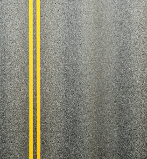 Asphalt road and double yellow lines dividing the lanes. stock photo