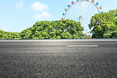 empty asphalt road and ferris wheel playgrounds with green tree in the city park