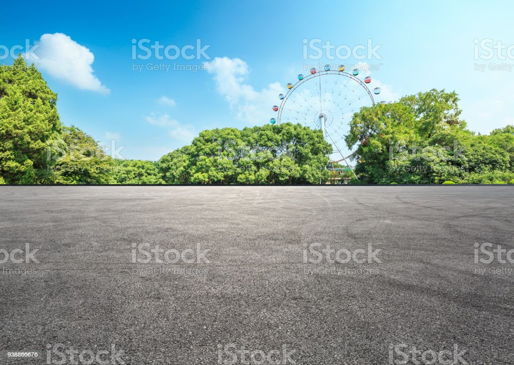 asphalt road and forest with playground ferris wheel stock photo