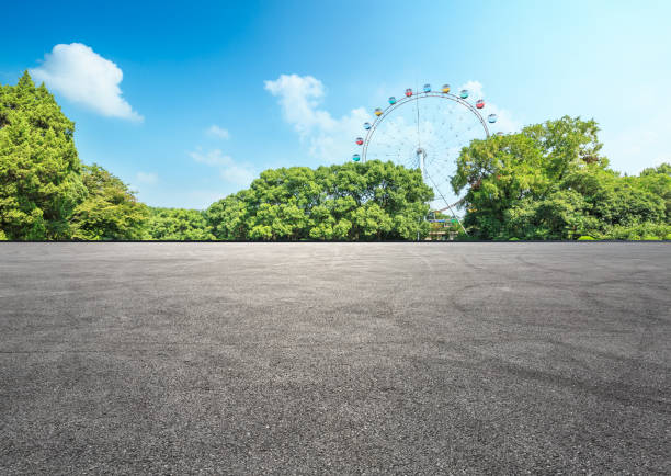 asphalt road and forest with playground ferris wheel empty asphalt road and forest with playground ferris wheel asphalt stock pictures, royalty-free photos & images