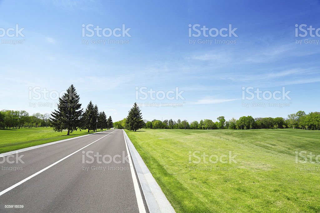 Asphalt road and grassy field stock photo