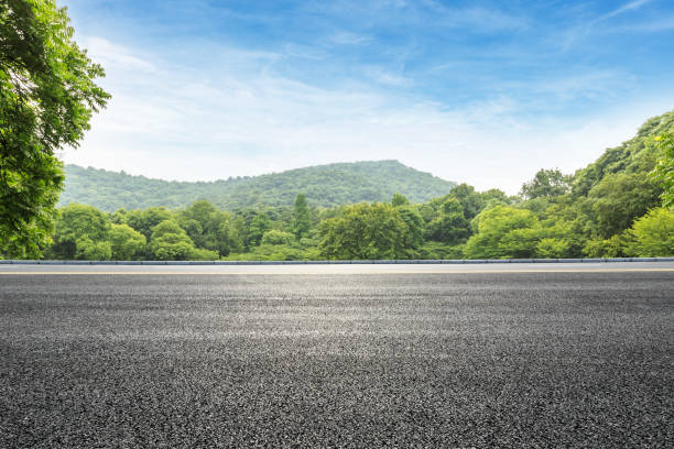 asphalt road and green forest with mountain landscape stock photo