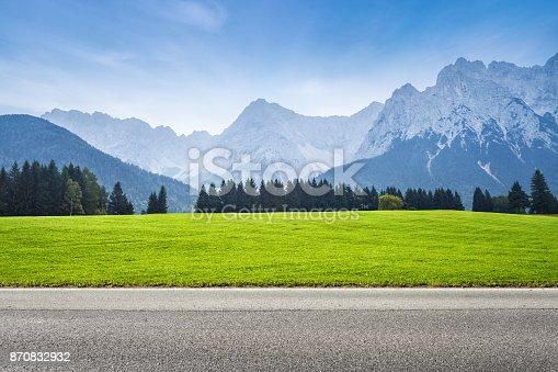 istock Asphalt road and green meadow 870832932