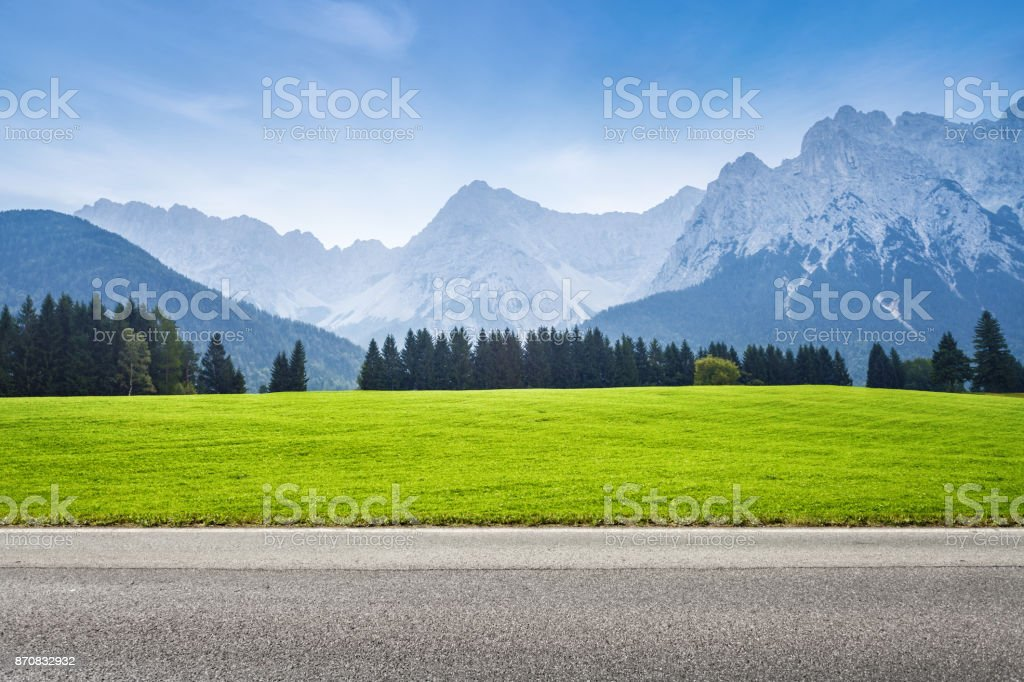 Asphalt road and green meadow stock photo