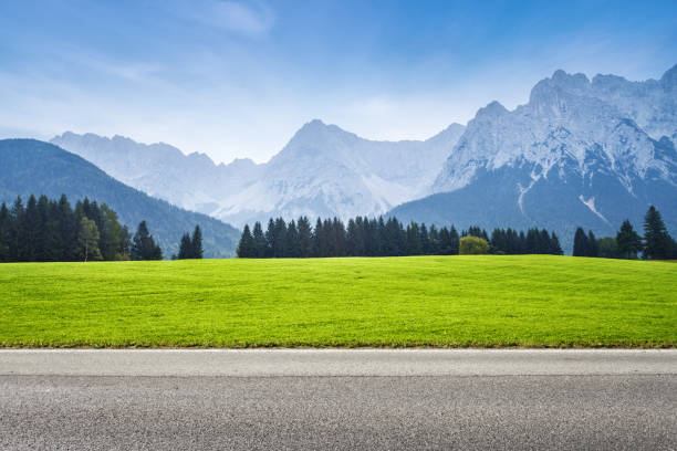 Asphalt road and green meadow alps mountains on background bavarian alps stock pictures, royalty-free photos & images