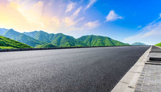 Asphalt road and green mountain nature landscape at sunset. stock photo