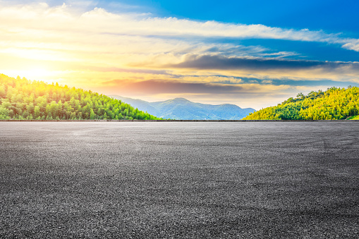 Asphalt road and green mountain with bamboo forest natural landscape at sunset.