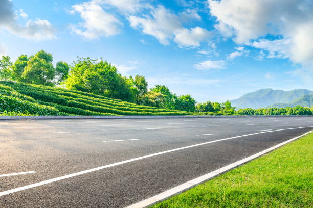 Asphalt road and green tea mountain nature landscape on sunny day. stock photo