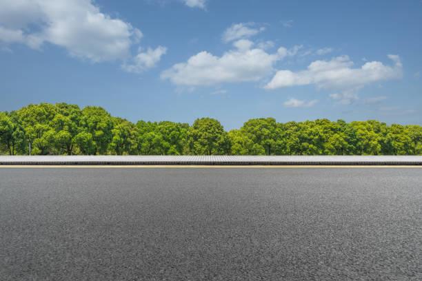 Asfaltweg en groene bomen onder de blauwe hemel foto
