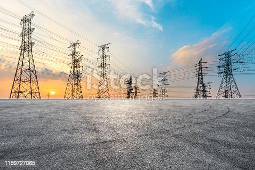 istock Asphalt road and high voltage power tower landscape 1159727065
