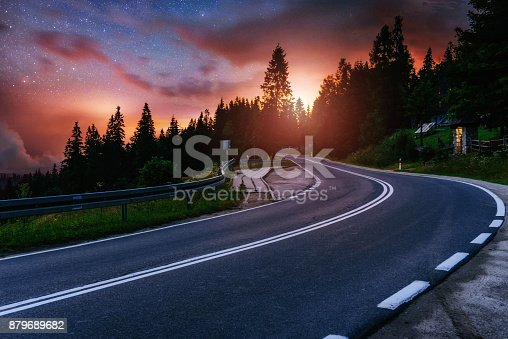 istock Asphalt road and lonely tree under a starry night sky and the Milky Way 879689682