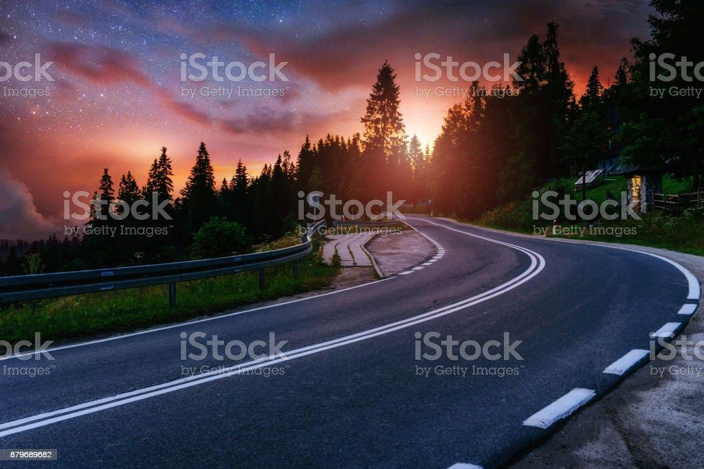 Asphaltierte Straße und einsame Baum unter einem Sternenhimmel und der Milchstraße – Foto