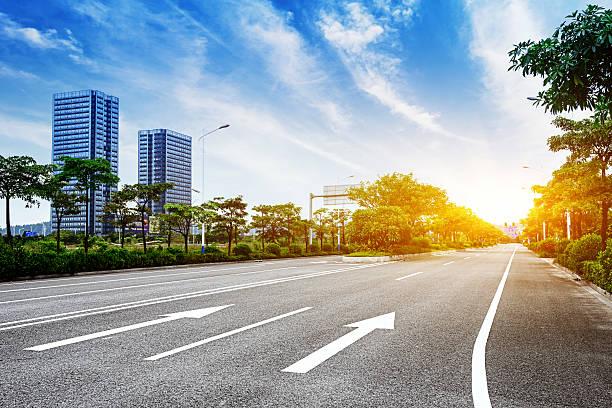 asphalt road and modern city - stadsweg stockfoto's en -beelden