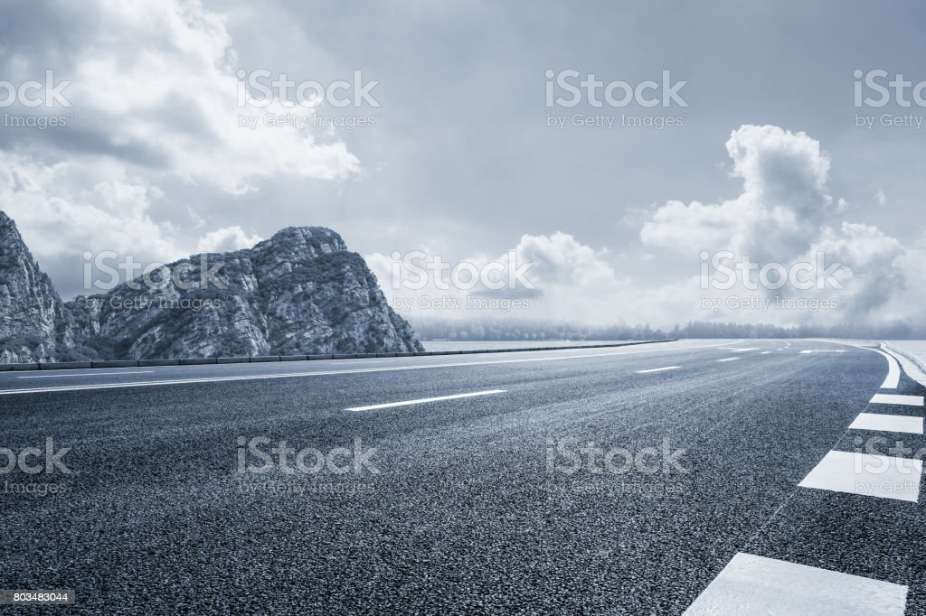 asphalt road and mountain under the blue sky stock photo