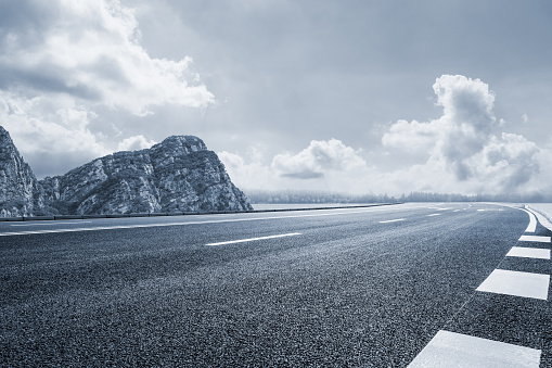 Asphalt Road And Mountain Under The Blue Sky Stock Photo - Download Image Now
