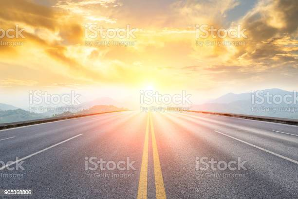 Photo of asphalt road and mountains with foggy landscape at sunset
