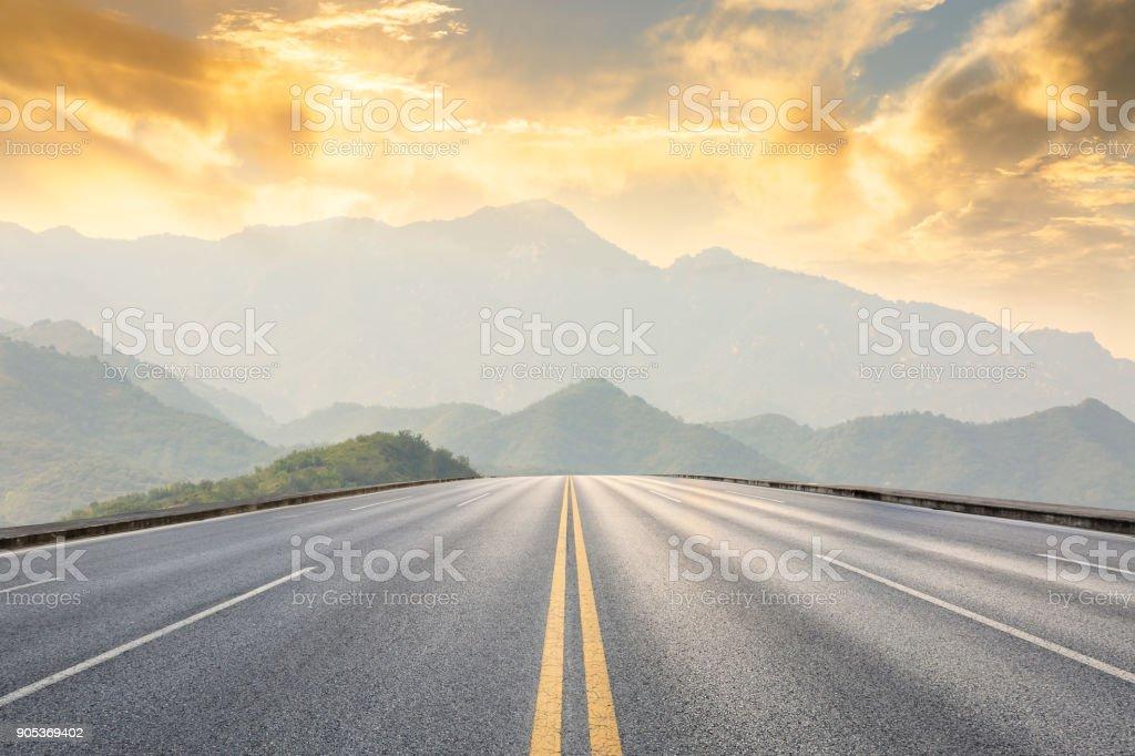 asphaltierte Straße und Berge mit nebligen Landschaft bei Sonnenuntergang - Lizenzfrei Abenddämmerung Stock-Foto