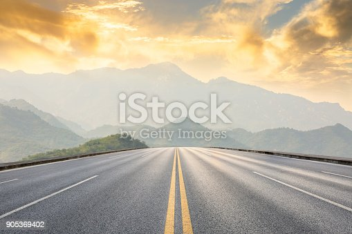 asphalt road and mountains with foggy nature landscape at sunset