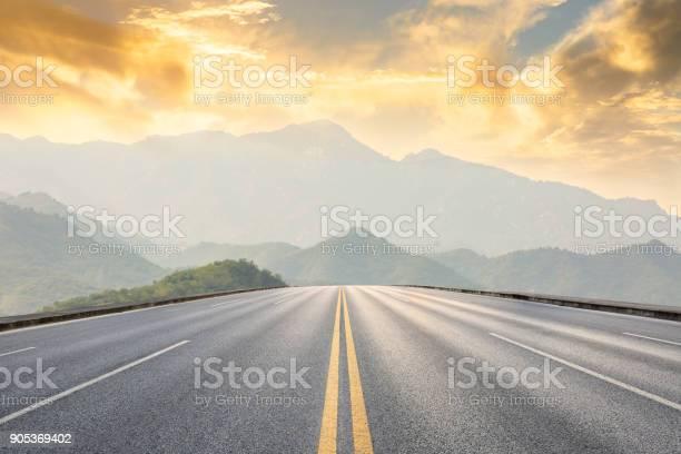 Asphalt road and mountains with foggy landscape at sunset picture id905369402?b=1&k=6&m=905369402&s=612x612&h=mwqflq8kd1wqjppvyuuk0yuv2dsb2freqdfslcwdvt0=