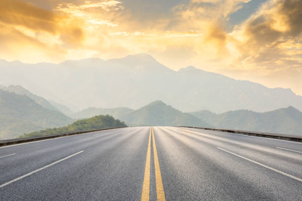 asphalt road and mountains with foggy landscape at sunset stock photo