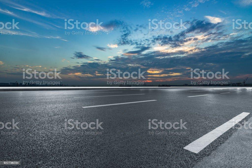 Asphalt road and sky cloud landscape at sunset stock photo