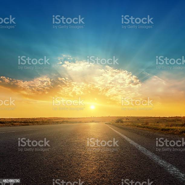 Photo of asphalt road and sunset in clouds