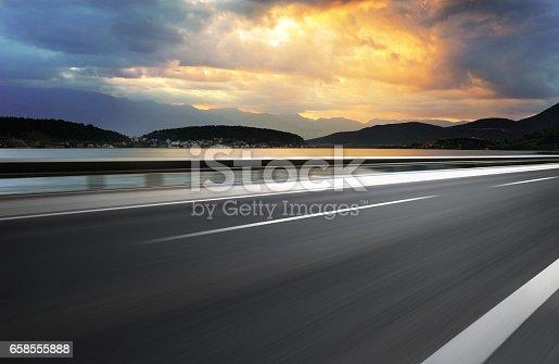istock Asphalt road beside lake 658555888