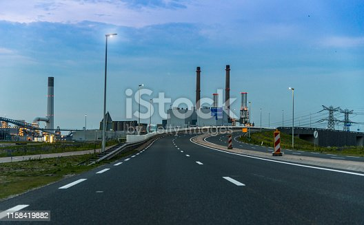 Empty asphalt road with an industrial plant on background