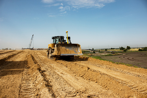 Asphalt road construction process. The bulldozer levels and compacts the clay soil for the base of the highway. Earthworks on a summer day.