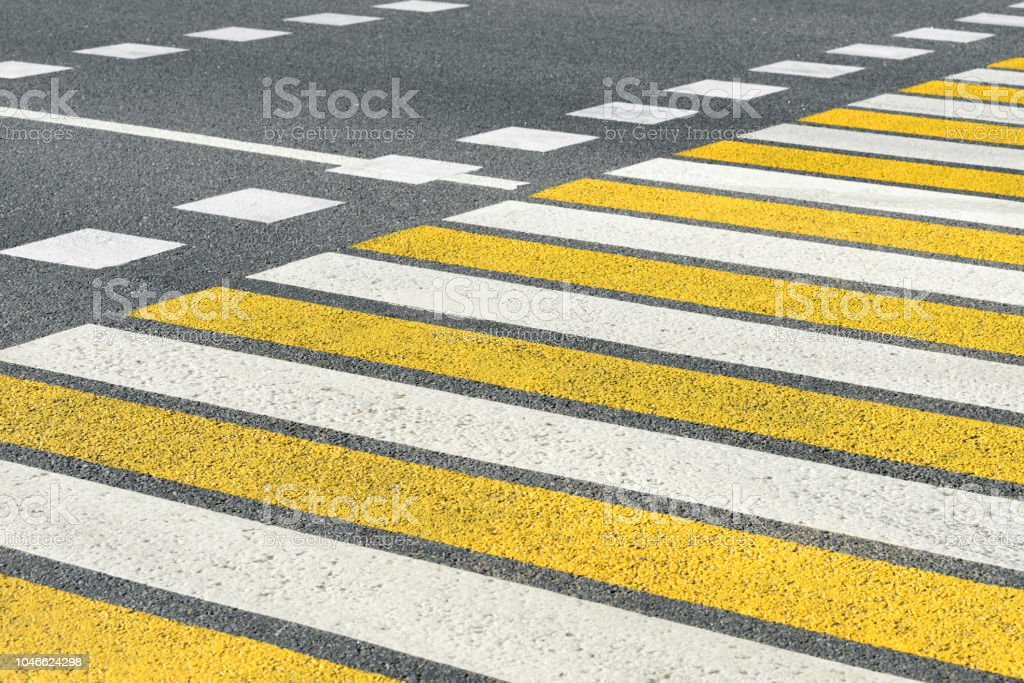 Asphalt road crosswalk with marking lines white and yellow stripes