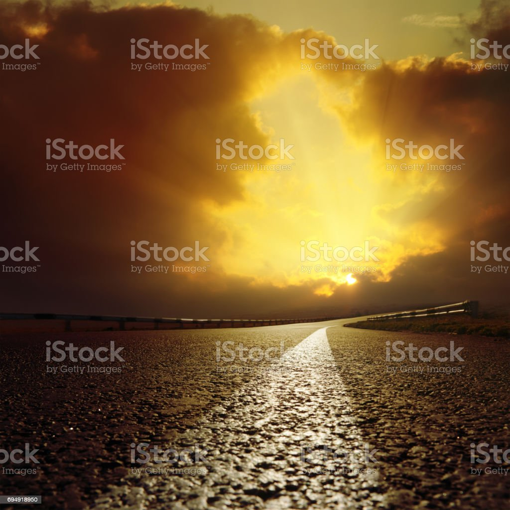 asphalt road goes to light in clouds stock photo