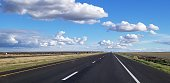 Asphalt Road going into the Horizon with a cloudy sky