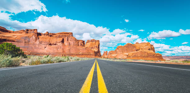 Asphalt road in Arches National Park Utah USA Asphalt road leading into Arches National Park, Utah, USA. delicate arch stock pictures, royalty-free photos & images