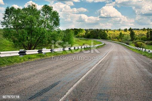 1155573645istockphoto Asphalt road in field by day 927970118