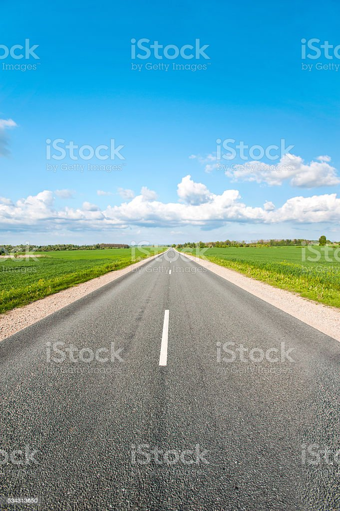 Asphalt road in green fields on blue cloudy sky background stock photo