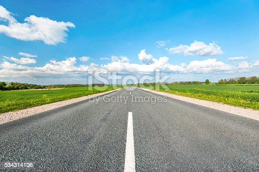 istock Asphalt road in green fields on blue cloudy sky background 534314106