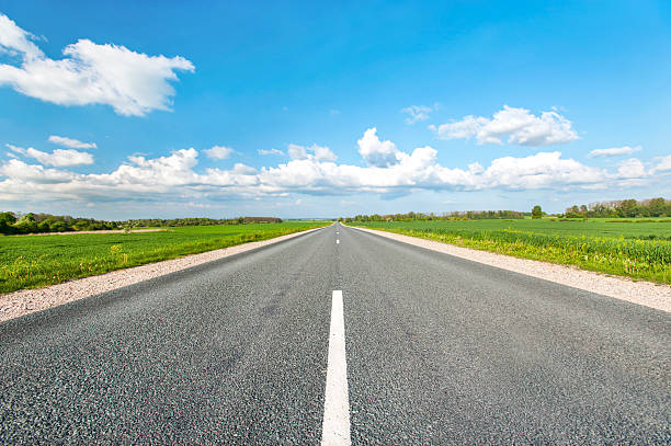 asphalt road in green fields on blue cloudy sky background - ufuk stok fotoğraflar ve resimler