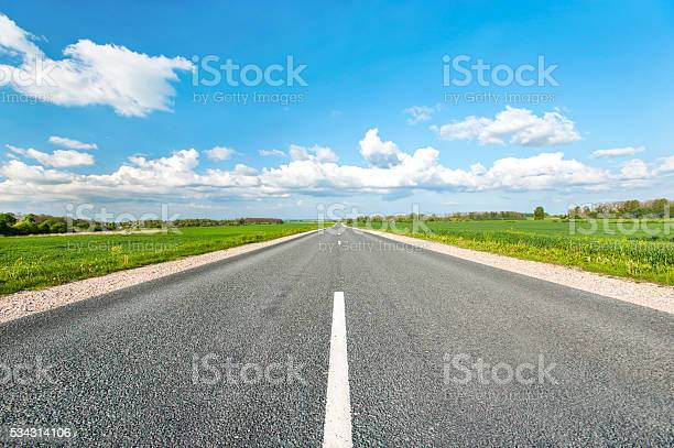 Photo of Asphalt road in green fields on blue cloudy sky background