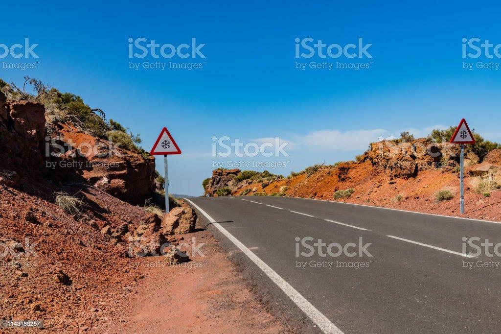 Asphalt road in mountain landscape - lava rock formation, El Teide...
