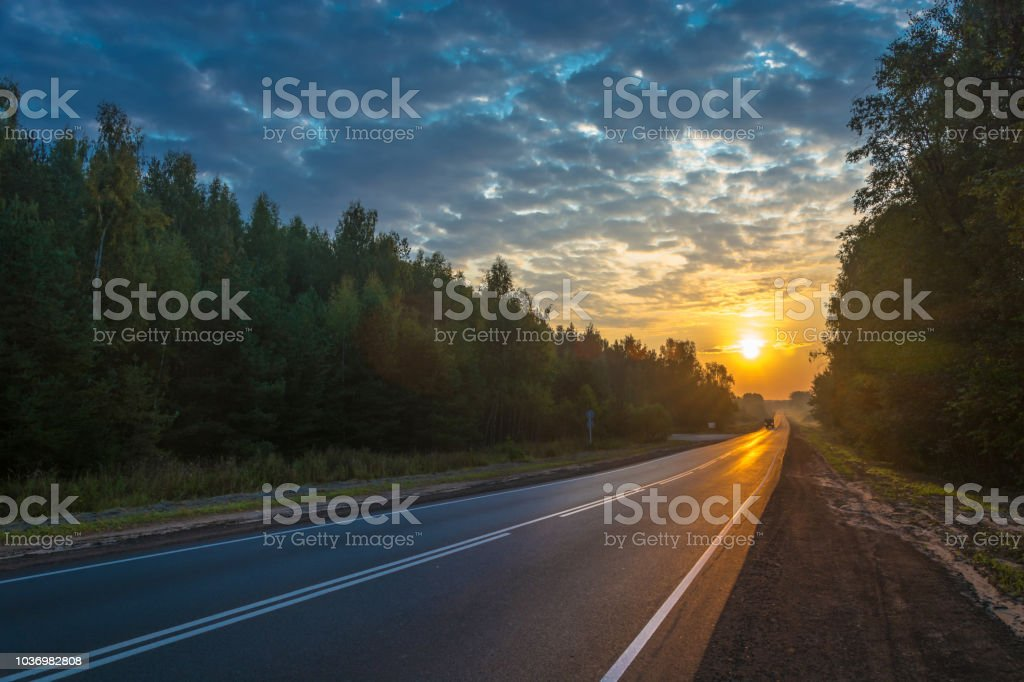 Asphalt road in the rays of the rising sun. стоковое фото