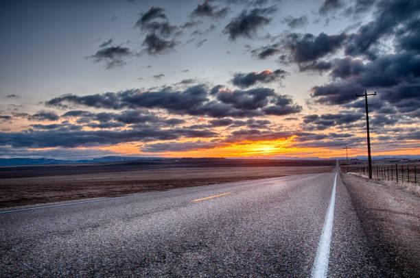 Asfalt weg die leidt naar de bewolkte horizon foto
